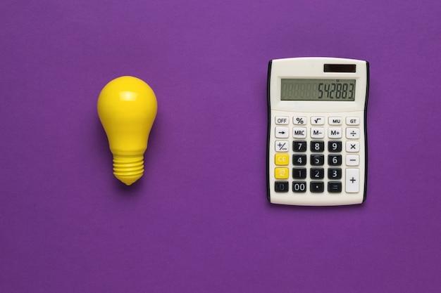 Klasyczny kalkulator i żółta żarówka na fioletowym tle.