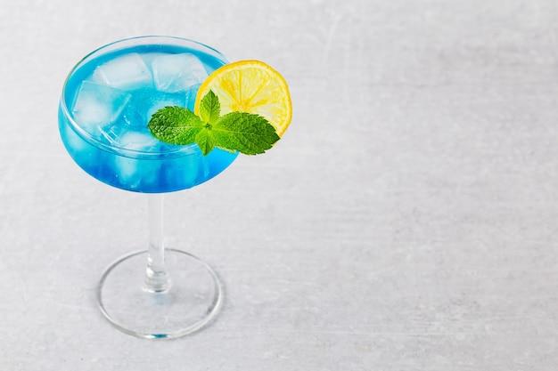 Klasyczny koktajl blue lagoon z cytryną na nowoczesnym na szarym tle