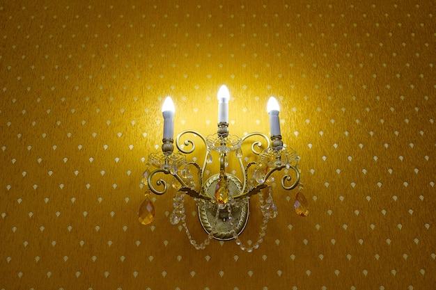 Klasyczny kryształowy kinkiet lub lampa na ścianie, na tle tapety z włączonymi światłami.