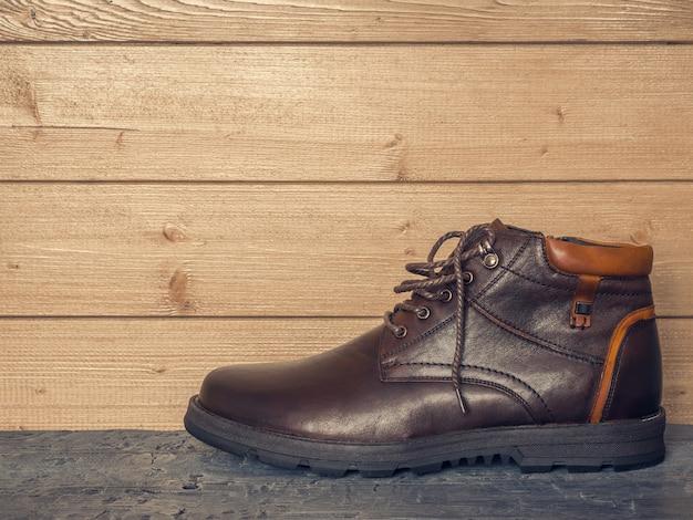 Klasyczny męski but z lewą stopą na drewnianej podłodze pod ścianą.