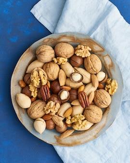 Klasyczny niebieski w jedzeniu. wymieszaj orzechy na talerzu - orzech, migdały, orzechy pekan, makadamia i nóż