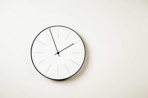 Klasyczny okrągły zegar ścienny na białym tle z miejsca kopiowania