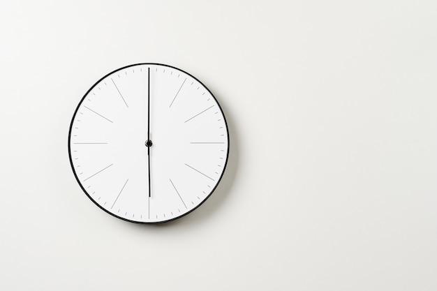 Klasyczny okrągły zegar ścienny na białym tle