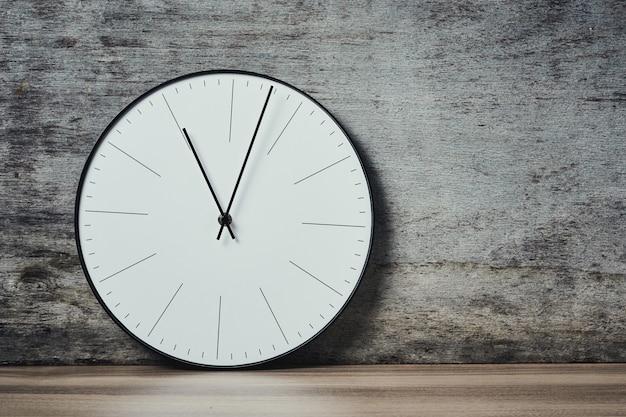 Klasyczny okrągły zegar ścienny na drewnianym tle z miejsca kopiowania
