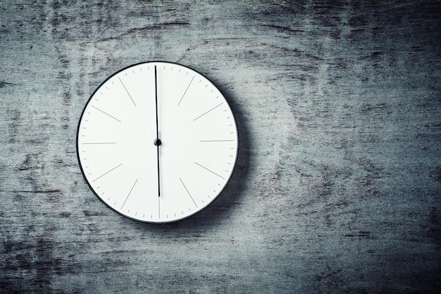 Klasyczny okrągły zegar ścienny na drewnianym tle z miejsca na kopię