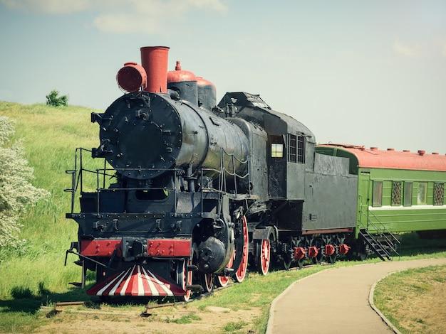 Klasyczny pociąg vintage z zielonym samochodem na torach w letni dzień.