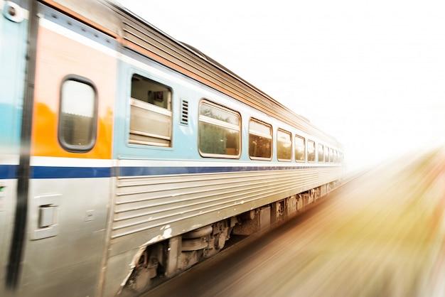 Klasyczny pociąg w ruchu z zachodem słońca. efekt rozmycia w ruchu. koncepcja pociągu prędkości. kopia przestrzeń.