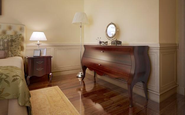 Klasyczny pokój o jasnobeżowych ścianach z sztukaterią i komodą ze stolikiem nocnym z ciemną drewnianą podłogą