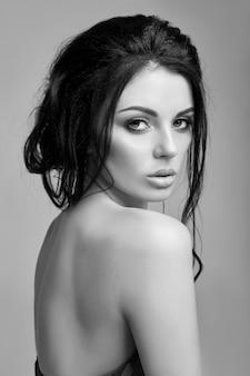 Klasyczny portret kobiety z idealnym makijażem wieczorowym, kobieta sukcesu na czarnym tle. idealna skóra bez zmarszczek, profesjonalny makijaż, długie rzęsy. idealna dziewczyna w czarnych ubraniach