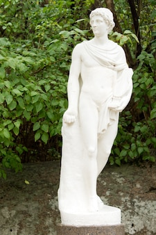 Klasyczny posąg greckiego lub rzymskiego boga stojącego w ogrodzie na tle zielonych liści