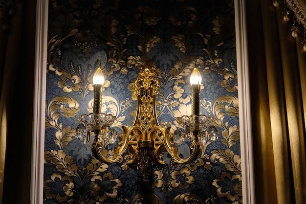 Klasyczny retro żyrandol kryształowy na ścianie, na tle tapety z włączonym światłem.