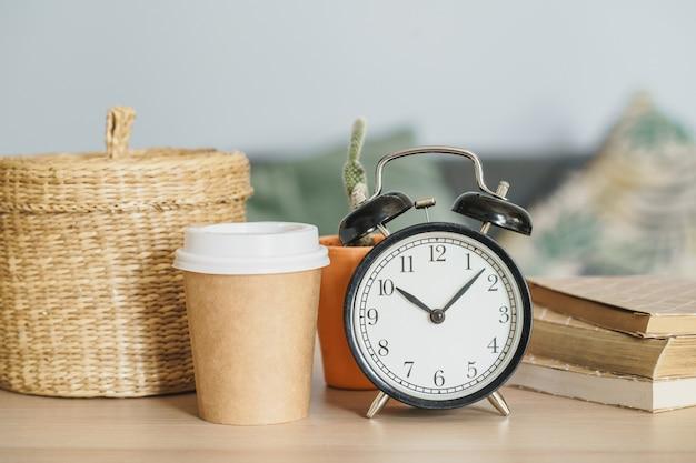 Klasyczny rocznika budzik, filiżanka kawy na drewnianym tle i