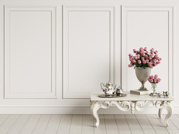 Klasyczny rzeźbiony stół z bukietem róż i srebrnym zestawem do kawy w klasycznym wnętrzu z miejscem na kopię