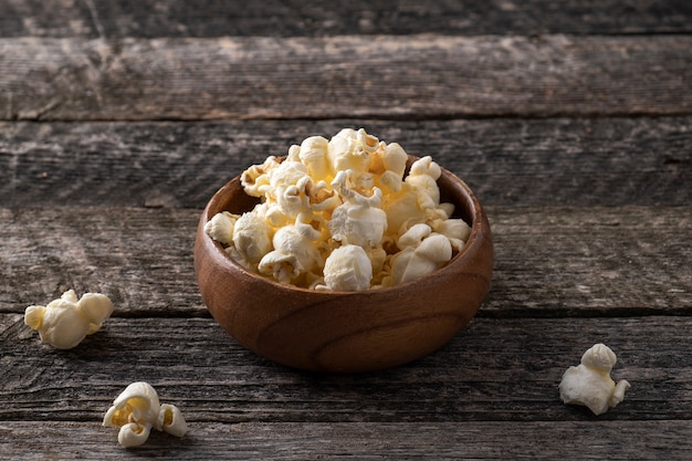 Klasyczny słony popcorn w drewnianej misce w stylu rustykalnym.