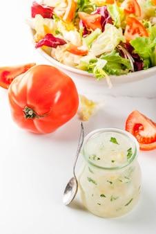 Klasyczny sos sałatkowy, domowy sos ranchowy z ziołami z oliwy z oliwek i cytryną, ze świeżymi warzywami na białym marmurowym stole,
