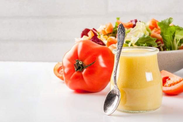Klasyczny sos sałatkowy z musztardą miodową, ze świeżymi warzywami na białym marmurowym stole,