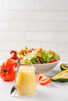 Klasyczny sos sałatkowy z musztardą miodową ze świeżymi warzywami na białym marmurowym stole