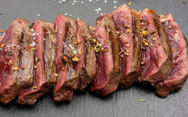 Klasyczny stek wołowy niegotowany (smażony na zewnątrz, czerwony w środku) z czerwonym sokiem, pokrojony na kawałki na czarnej desce, gotowość krwiste, zbliżenie
