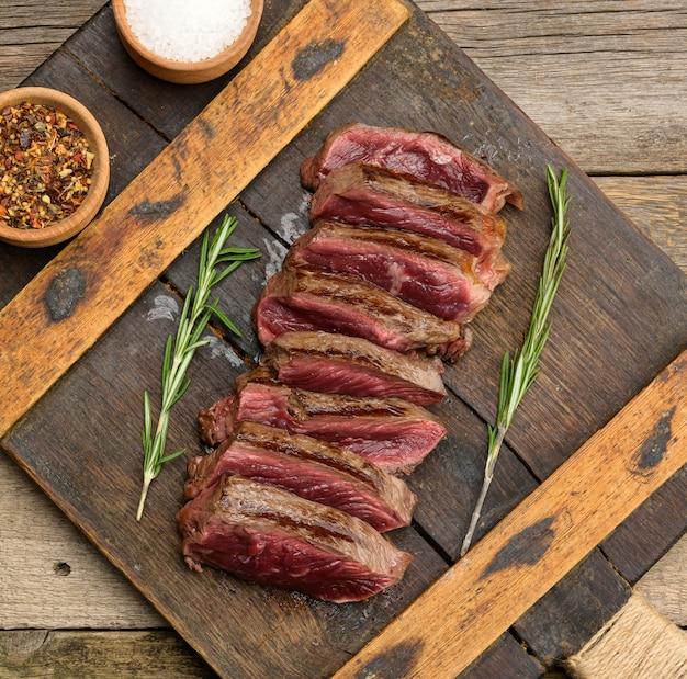 Klasyczny stek wołowy surowe mięso smażone na zewnątrz czerwone w środku z czerwonym sokiem pokrojone na kawałki