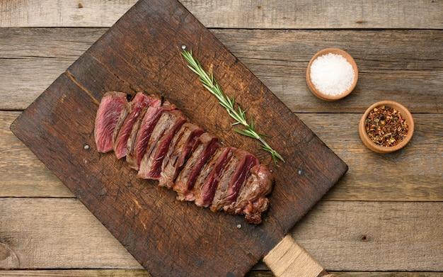 Klasyczny stek z surowego mięsa wołowego, smażony na zewnątrz, czerwony w środku, z czerwonym sokiem, pokrojony na kawałki na drewnianej desce. gotowość rzadko