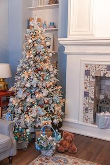 Klasyczny świąteczny wystrój pokoju, noworoczne drzewo ze srebrnymi dekoracjami. nowoczesny niebieski apartament w stylu klasycznym z kominkiem i choinką. wigilia w domu.