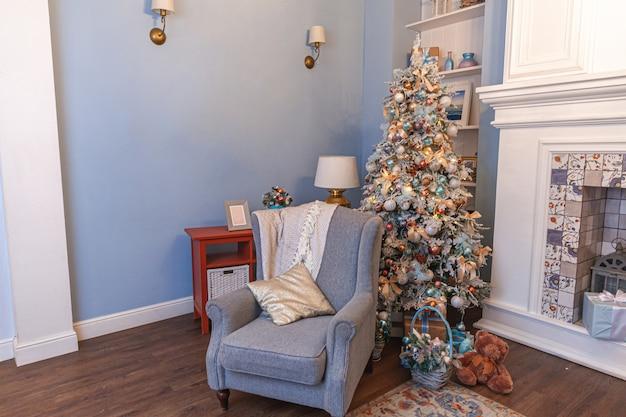 Klasyczny świąteczny wystrój pokoju, noworoczne drzewo ze srebrnymi dekoracjami. nowoczesny niebieski apartament w stylu klasycznym z kominkiem i fotelem. wigilia w domu.