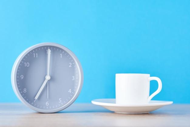 Klasyczny szary budzik i biała filiżanka kawy na niebiesko