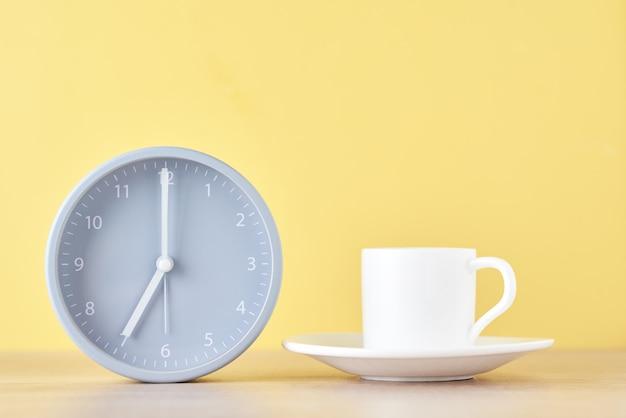 Klasyczny szary budzik i biała filiżanka kawy na żółtym tle