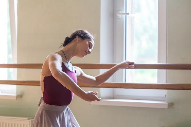 Klasyczny tancerz baletowy pozowanie w barre na sali prób