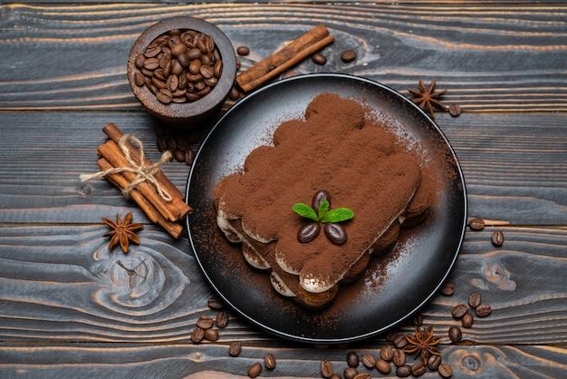 Klasyczny tiramisu deser na ceramicznym talerzu na drewnianym tle