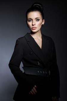 Klasyczny uroda portret kobiety z doskonały makijaż wieczorowy na ciemnym tle. idealna skóra bez zmarszczek, profesjonalny makijaż kosmetyczny, długie rzęsy. idealna dziewczyna w czarnych ubraniach