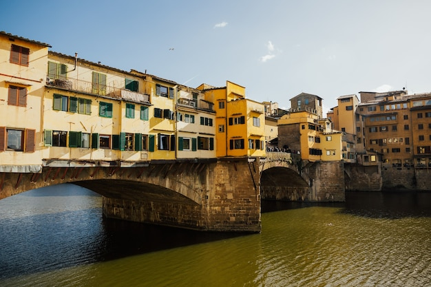 Klasyczny widok na słynny ponte vecchio ze słynną rzeką arno w historycznym centrum miasta