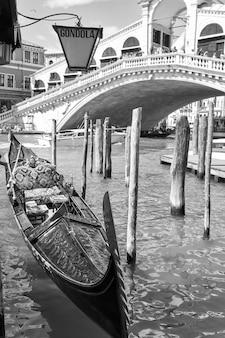 Klasyczny widok wenecji z zacumowaną gondolą w pobliżu mostu rialto, włochy. obraz czarno-biały