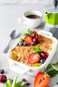 Klasyczny włoski deser tiramisu ozdobiony truskawkami, wiśniami i miętą na białym tle.