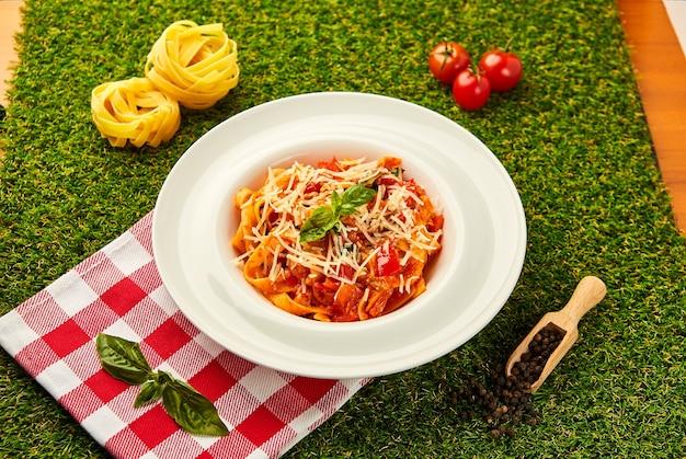 Klasyczny włoski makaron arrabbiata z bazylią i świeżo parmezanem na zielonej trawie