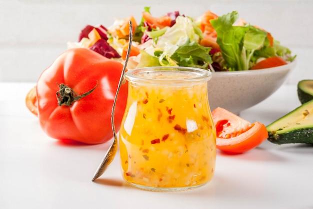Klasyczny włoski sos sałatkowy z winegretem, ze świeżymi warzywami na białym marmurowym stole,