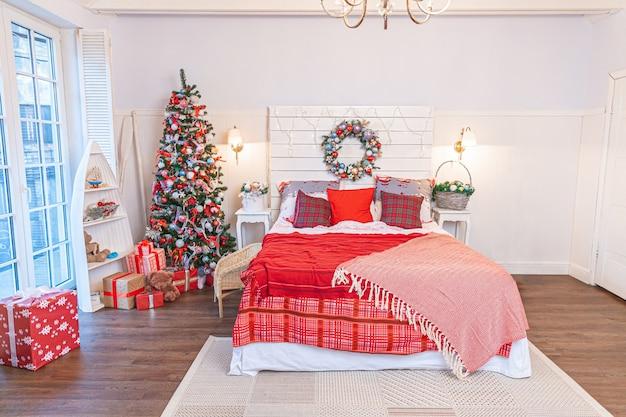 Klasyczny wystrój pokoju z choinką i tradycyjnymi biało czerwonymi dekoracjami. nowoczesna, czysta biała sypialnia w stylu klasycznym. wigilia w domu. minimalistyczny projekt domu.