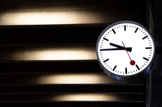 Klasyczny zegar powiesić na ścianie cementu.