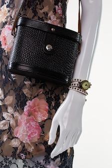 Klasyczny zegarek na dłoni manekina. żeński manekin z małym zegarkiem. modne damskie dodatki w stylu retro. mały zegarek na rękę i sukienka.
