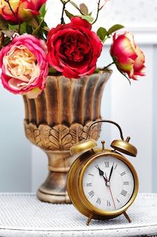 Klasyczny zegarek z zegarem w jasnym kolorowym wnętrzu retro za czerwonymi kwiatami