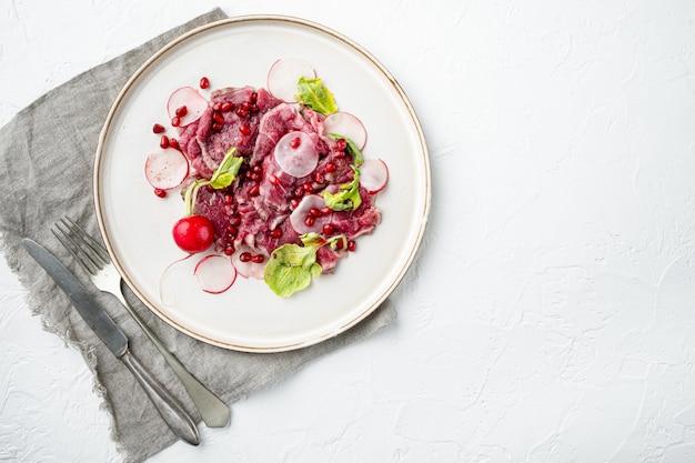 Klasyczny zestaw carpaccio z wołowiny, z rzodkiewką i granatem, na talerzu, na białym kamieniu