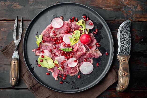Klasyczny zestaw carpaccio z wołowiny, z rzodkiewką i granatem, na talerzu, na starym ciemnym drewnianym stole