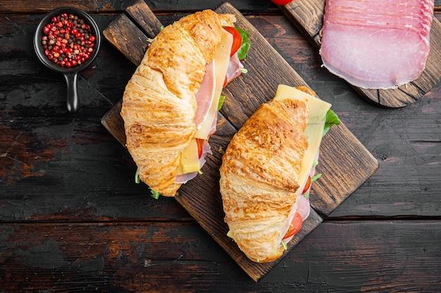 Klasyczny zestaw kanapek z rogalikami blt, z ziołami i składnikami, na tle starego ciemnego drewnianego stołu, płaski widok z góry