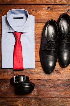 Klasyczny zestaw męski. koszula pasek do butów na drewnianym biurku