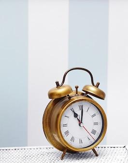 Klasyczny złoty zegarek w jasnym kolorowym wnętrzu retro