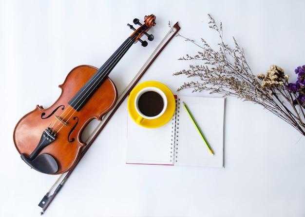 Klasyka skrzypce z kokardką umieścić obok żółtej ceramicznej filiżanki kawy