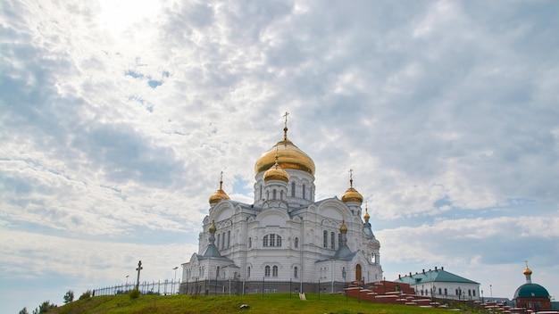 Klasztor belogorsky na tle błękitnego nieba z chmurami