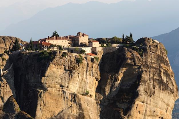 Klasztory meteory w grecji w wysokich górach na zachód słońca, tło