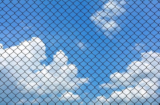 Klatka metalu drut na niebieskim niebie z chmurą w lecie - tło