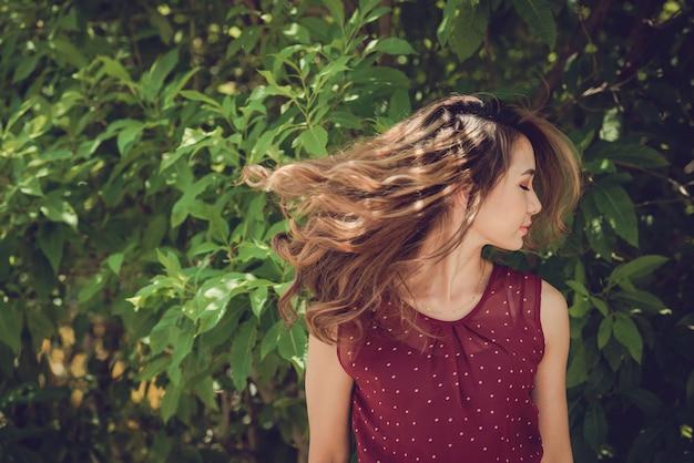 Klatka piersiowa strzelająca dziewczyna rzucająca głową z zamkniętymi oczami w słońcu